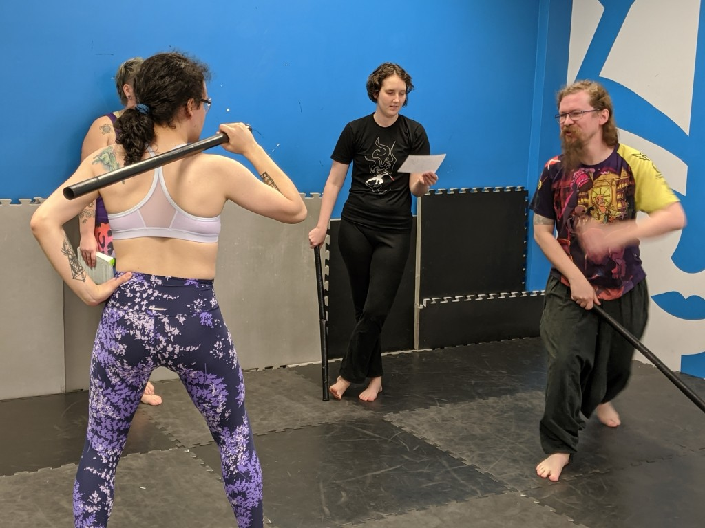 A group of students work through their own interpretation of a historical swordplay technique.